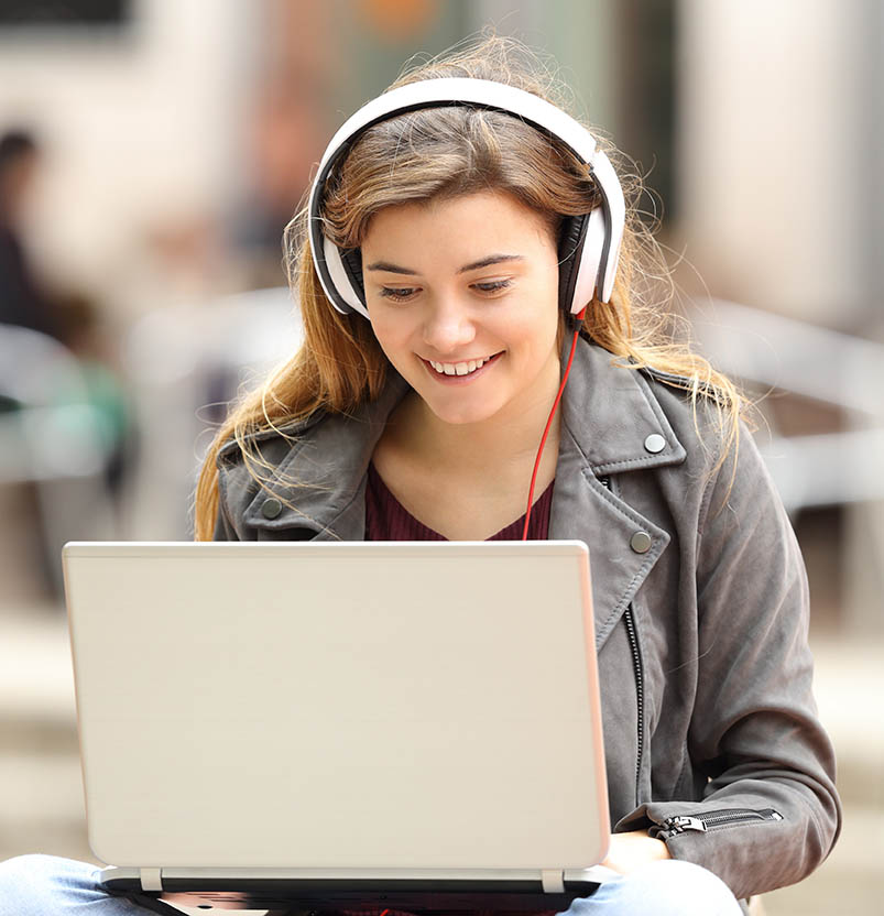 Young female wearing headphones at a laptop
