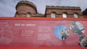Writing and images on a large permenent exhibition with Inverness Castle building in the background